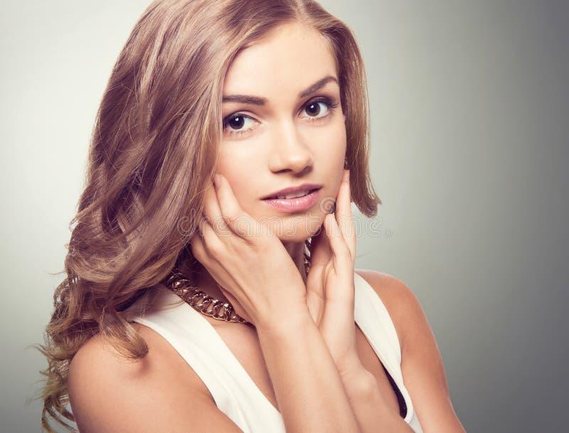 Nette Blondine mit braunen Augen und den langen gelockten Haaren lizenzfreies stockbild