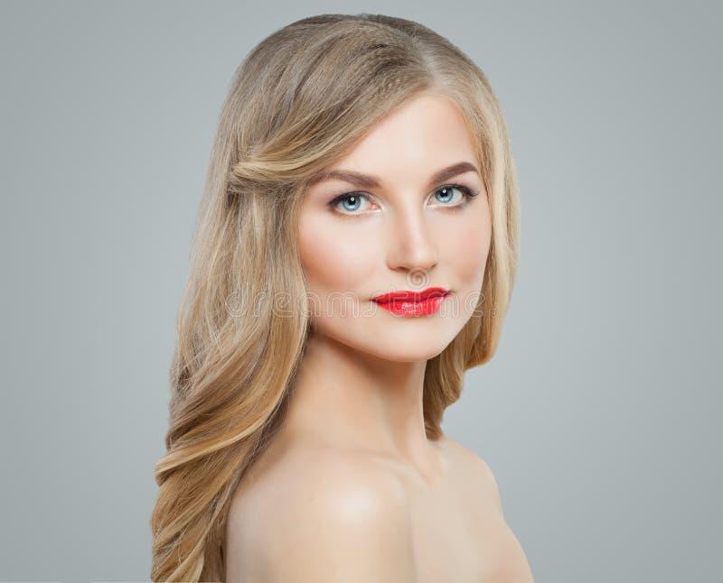 Nette Blondine mit dem langen gelockten Haar, klarer Haut und rotem Lippenmake-up Gesichtsbehandlung, Haarpflege und Cosmetology lizenzfreies stockbild