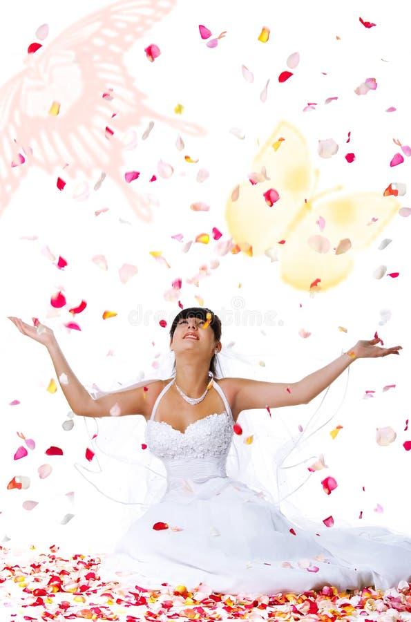 Nette Braut wirft rosafarbene Blumenblätter und butterflys stockfoto