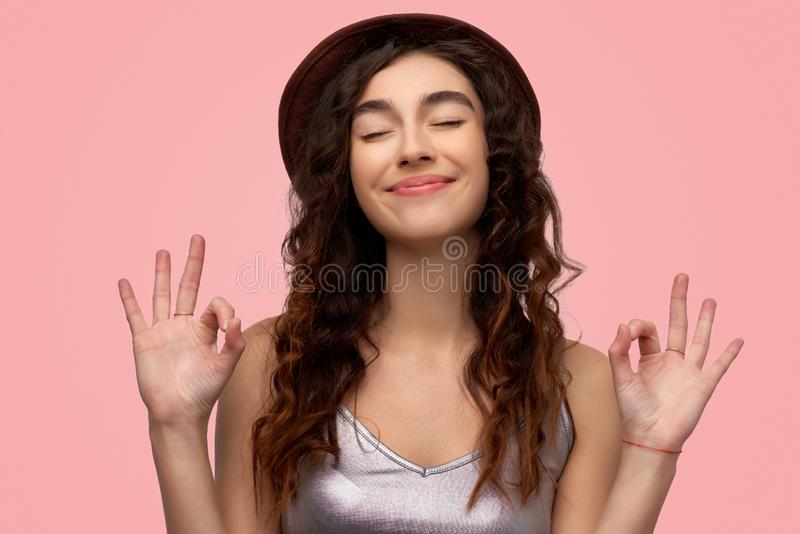 Nette brunette junge Frau mit frohem Ausdruck, zeigt O.K.zeichen mit beiden Händen, gekleidet im zufälligen weißen Hemd stockfoto