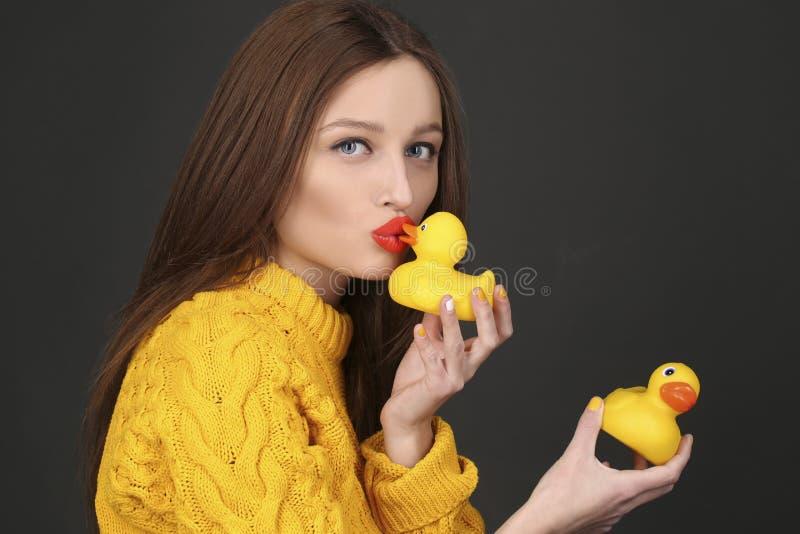 Nette Brunettefrau mit den roten Lippen gelbe Gummienten küssend stockfotos