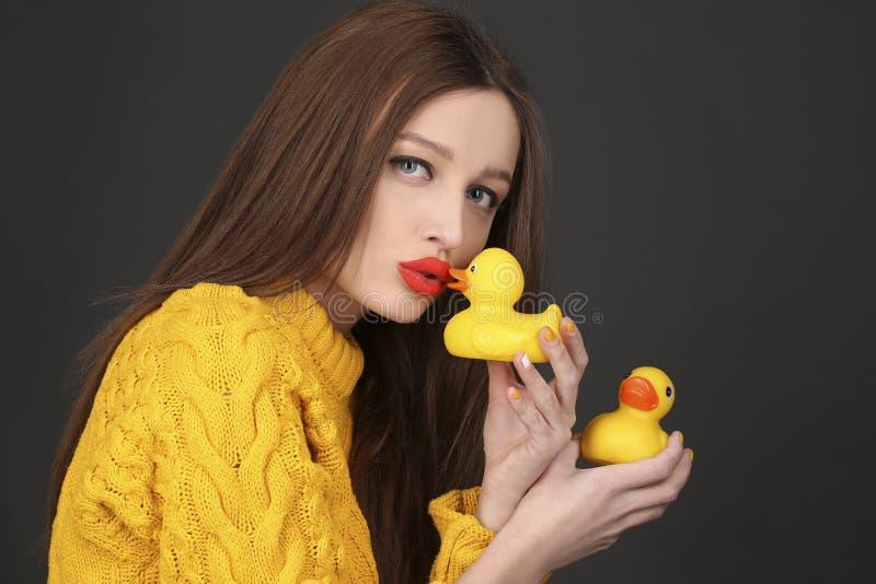 Nette Brunettefrau mit den roten Lippen gelbe Gummienten küssend lizenzfreies stockfoto