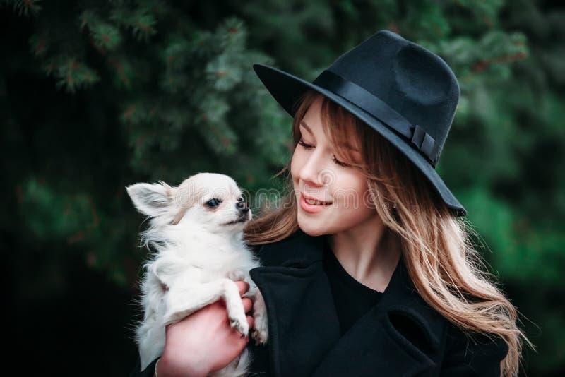 Nette nette dünne kaukasische Mädchenblondine mit dem langen Haar in einem schwarzen Mantel und in einem schwarzen Hut herein am  lizenzfreie stockfotos