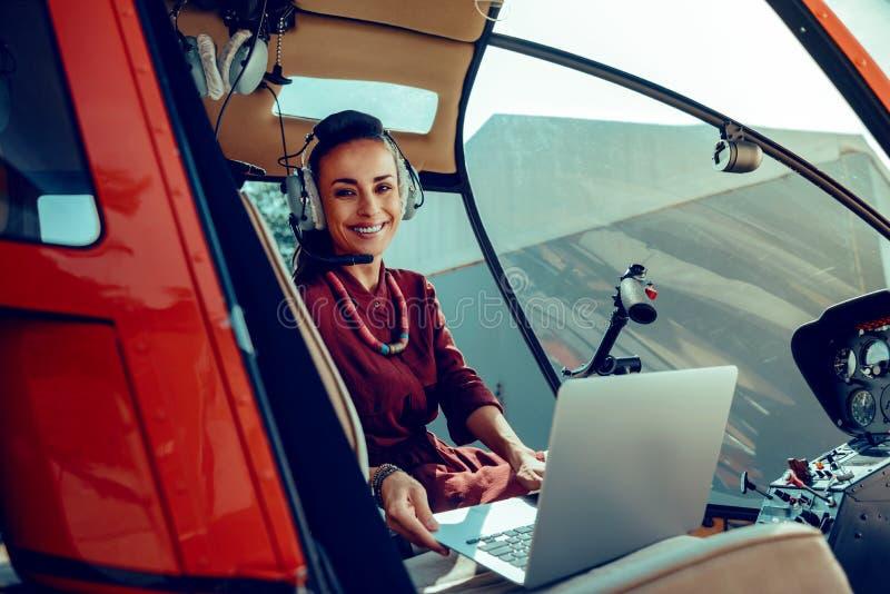 Nette dunkelhaarige Frau mit dem breiten L?cheln, das silbernen Laptop auf vorderen Sitz setzt stockfotografie