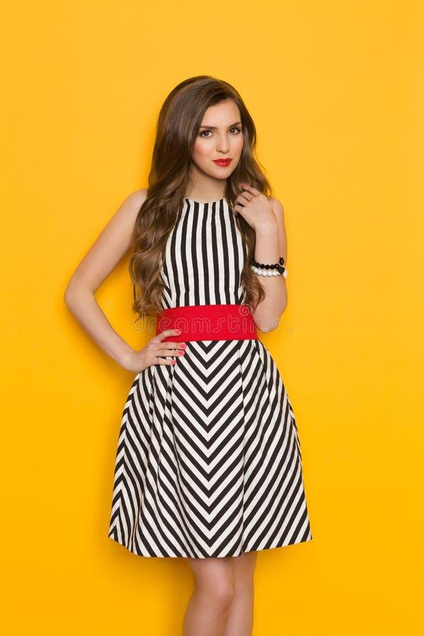 Nette elegante Frau in gestreiftem Kleid stockfoto