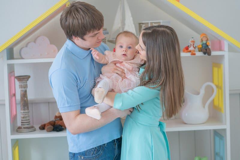 Nette engverbundene Familie der Mutter, des Vatis und der Tochter, die in ihrem Reinraum aufwerfen lizenzfreie stockbilder