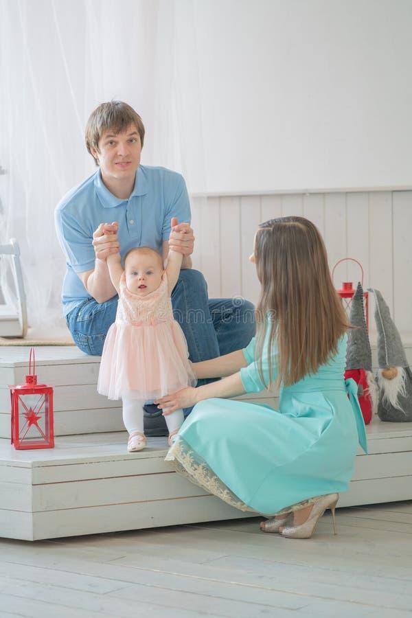 Nette engverbundene Familie der Mutter, des Vatis und der Tochter, die in ihrem Reinraum aufwerfen lizenzfreie stockfotografie