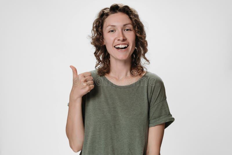 Nette enthusiastische erfreute junge kaukasische gelockte Frau, die Daumen herauf Geste zeigt lizenzfreie stockfotografie