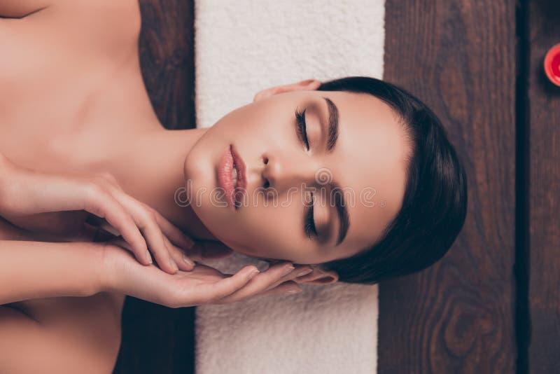Nette entspannte junge Frau, die in Badekurortsalon mit geschlossenen Augen legt lizenzfreie stockfotos
