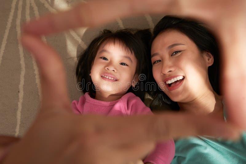 Nette ethnische Frau mit Tochter lizenzfreie stockfotos