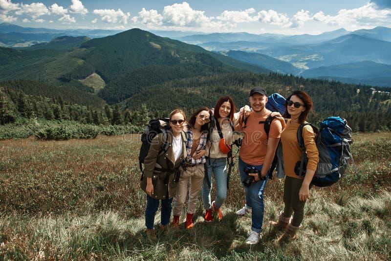 Nette fünf Touristen haben Spaß in den Bergen lizenzfreies stockbild