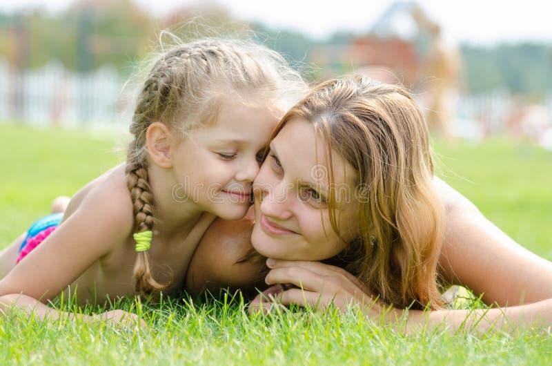 Nette Fünfjahrestochter bedrängte ihr Gesicht zum mother& x27; s-Gesicht auf einem Rasen des grünen Grases lizenzfreies stockfoto