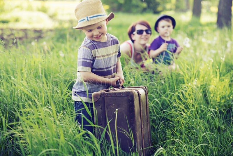 Nette Familie, die auf hohem Gras spielt lizenzfreies stockfoto