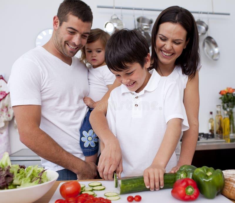 Nette Familie, die zusammen in der Küche kocht stockbild