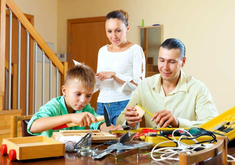 Nette Familie, die zusammen etwas mit Arbeitsgeräten macht stockfotografie