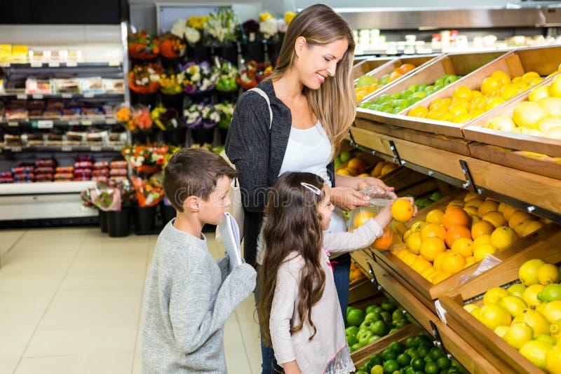 Nette Familie, die zusammen Lebensmittelgeschäfte wählt lizenzfreies stockfoto