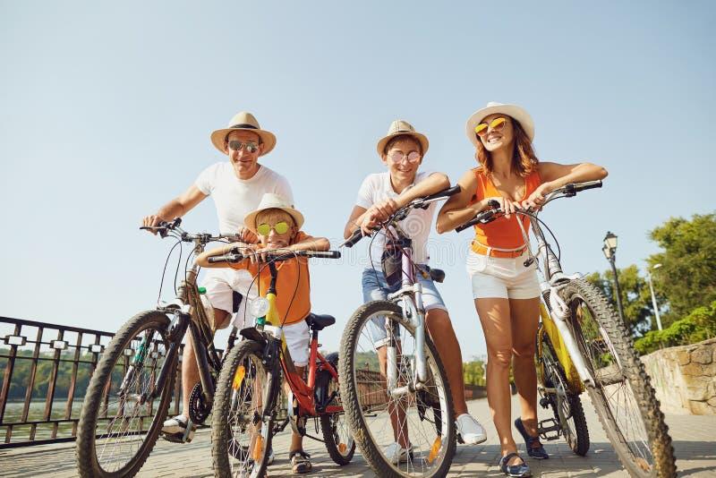 Nette Familie mit den Fahrrädern, die auf Damm stehen lizenzfreie stockbilder