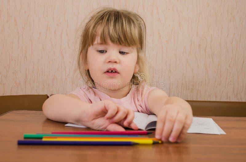 Nette Farben und Stümper des kleinen Mädchens mit farbigen Bleistiften und Scheren stockbilder