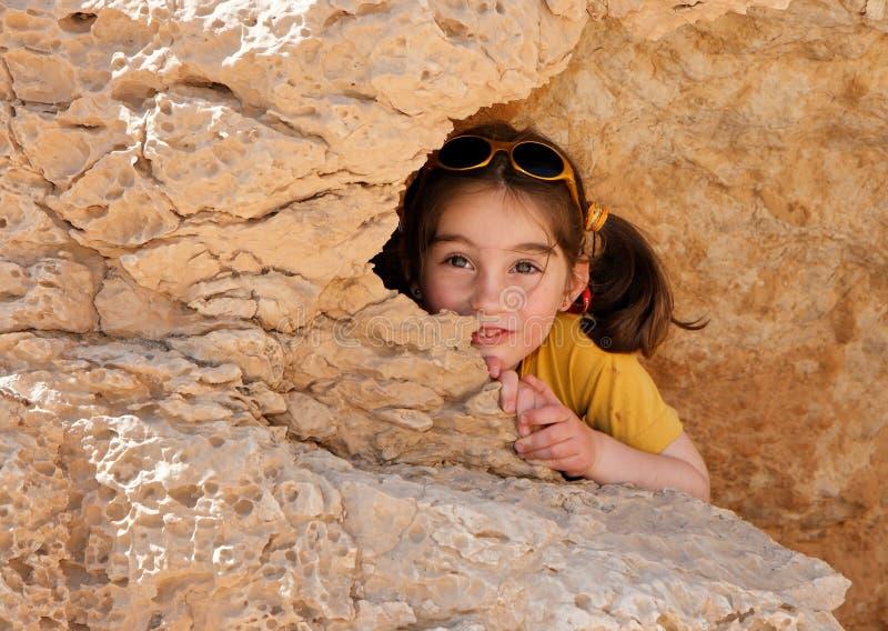 Nette Felle des kleinen Mädchens hinter einem Felsen stockfotografie