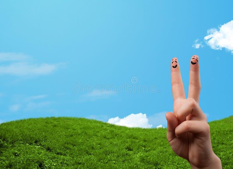 Nette Fingersmiley mit Landschaftslandschaft am Hintergrund lizenzfreie stockbilder