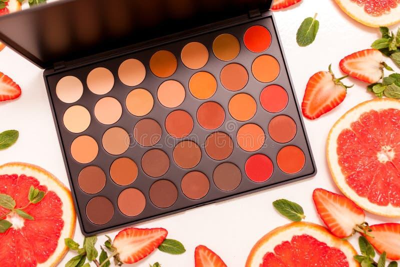 Nette flache Lage mit Palette von Kosmetik mit frischer Frucht, geschnittene Erdbeeren und Pampelmuse oder rote Orange, Minzenblä stockfotos