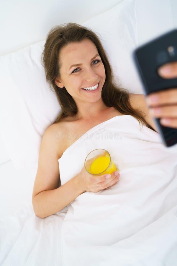 Nette Frau überprüft den Smartphone und trinkt Orangensaft im Bett stockfotografie