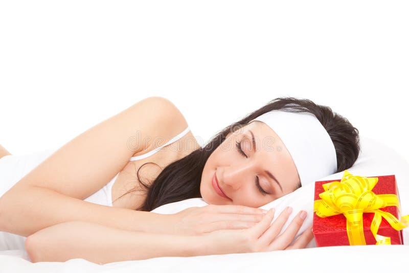 Nette Frau auf dem Bett mit Geschenkkasten stockbild