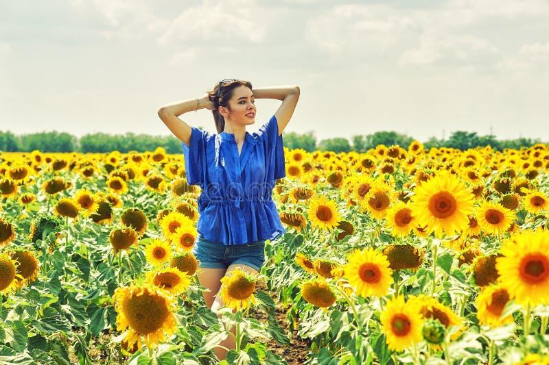 Nette Frau auf einem Sommerweg auf dem Gebiet mit Sonnenblumen lizenzfreie stockfotografie