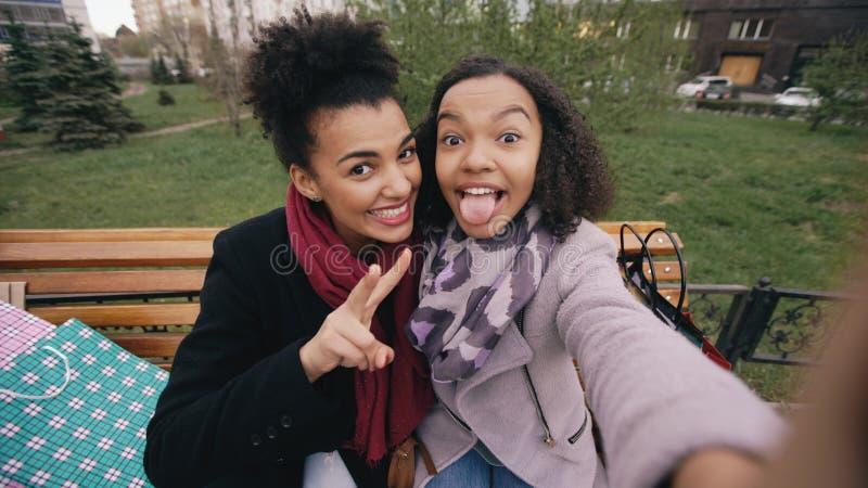 Nette Frau des Afroamerikaners zwei, die selfie auf Smartphone mit Einkaufstaschen und dem Lächeln nimmt Freundinnen, die an sitz stockfoto