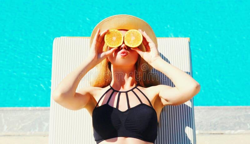 Nette Frau des Porträts, die in ihren Handscheiben der Orange ihre Augen auf Pool des blauen Wassers versteckend hält lizenzfreie stockbilder