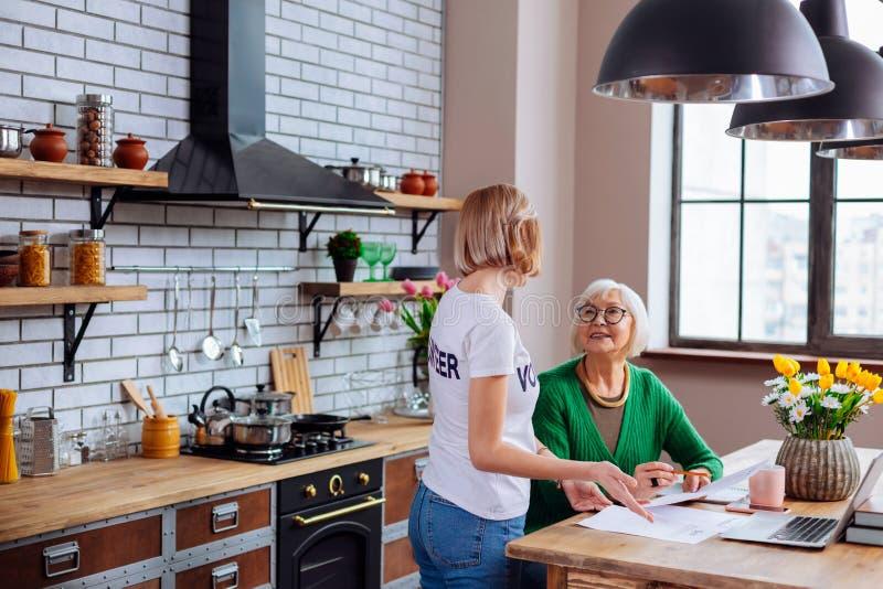 Nette Frau, die ältere Freifraueinzelteile der überfälligen Darlehensmitteilung erklärt stockbilder
