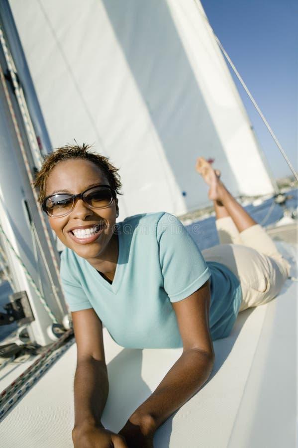Nette Frau, die auf der Yacht liegt lizenzfreie stockfotos