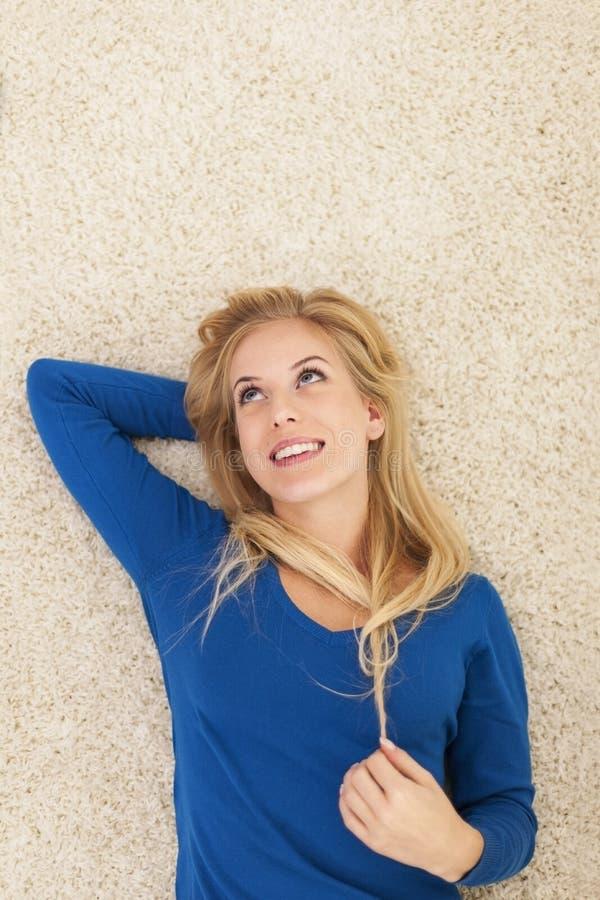 Nette Frau, die auf Teppich sich entspannt lizenzfreies stockfoto
