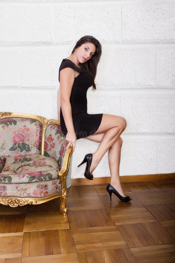Nette Frau, die auf Wohnzimmer sitzt stockbild