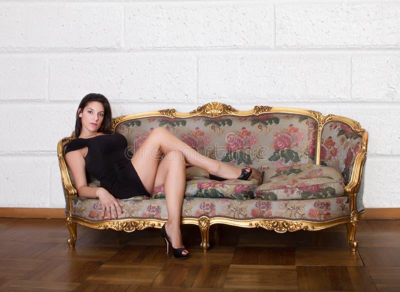Nette Frau, die auf Wohnzimmer sitzt stockfotos