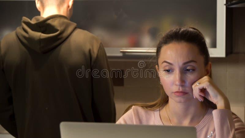 Nette Frau, die an dem Laptop in der Küche während ihre Freundstellung macht ihr coffe oder Tee arbeitet Mann, der einen Becher s lizenzfreies stockfoto