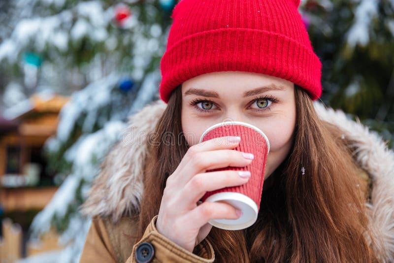 Nette Frau, die draußen heißen Kaffee im Winter trinkt stockbild