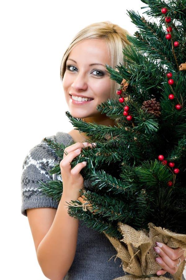 Nette Frau, die ein christmastree lächelt und anhält stockbild