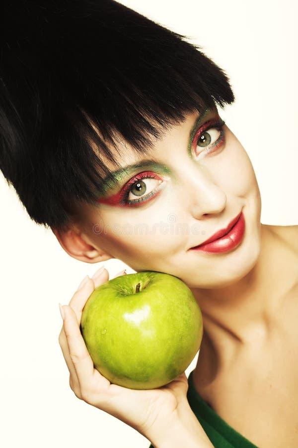 Nette Frau, die grünen Apfel hält stockbild