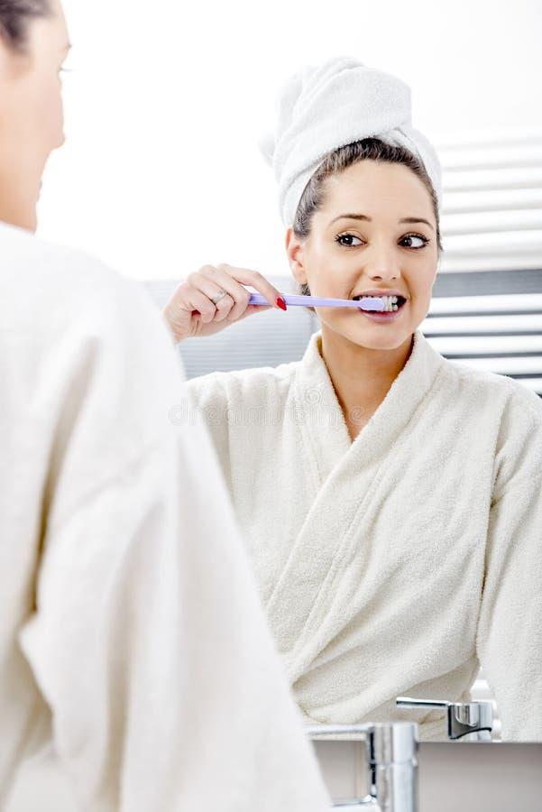 Nette Frau, die ihre Zähne säubert stockbilder