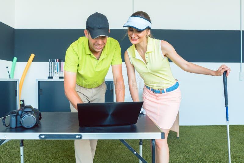 Nette Frau, die ihren notierten Videostreik während einer Golfklasse aufpasst stockbild