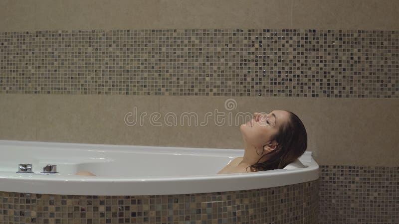 Nette Frau, die im Badezimmer sich entspannt stockfotografie