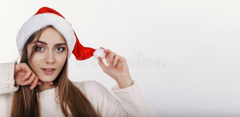 Nette Frau, die Kamera betrachtet und ihren Weihnachtshut toching lizenzfreie stockfotos