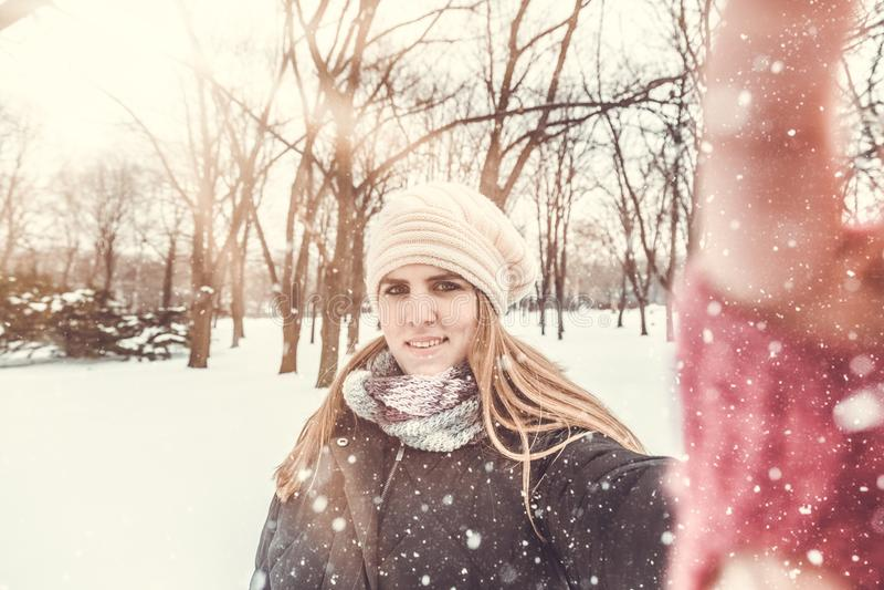 Nette Frau, die Selbstporträt durch die Anwendung ihres intelligenten Telefons am schneebedeckten Tag nimmt stockbild