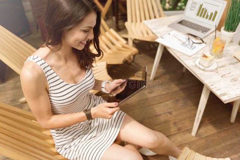 Nette Frau, die Tablette verwendet lizenzfreie stockfotos