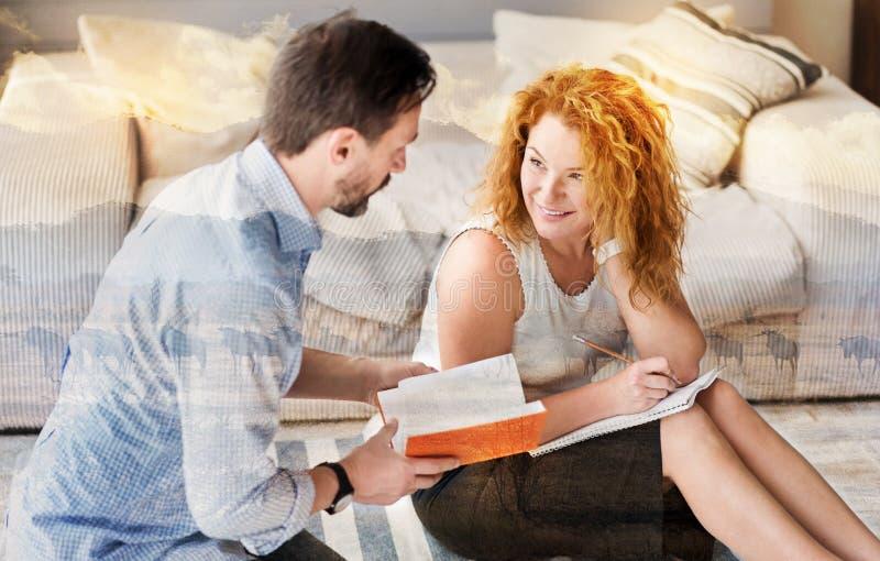 Nette Frau, die zu ihrem Ehemann beim zu Hause arbeiten lächelt lizenzfreies stockfoto