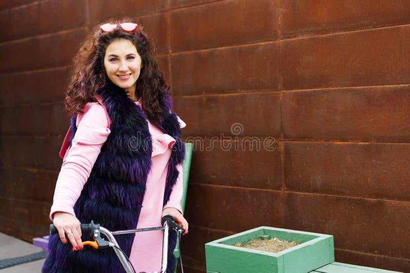 Nette Frau in einem rosa Kleid und purpurroten in einem Pelzkap, die einen Roller reiten stockfotografie
