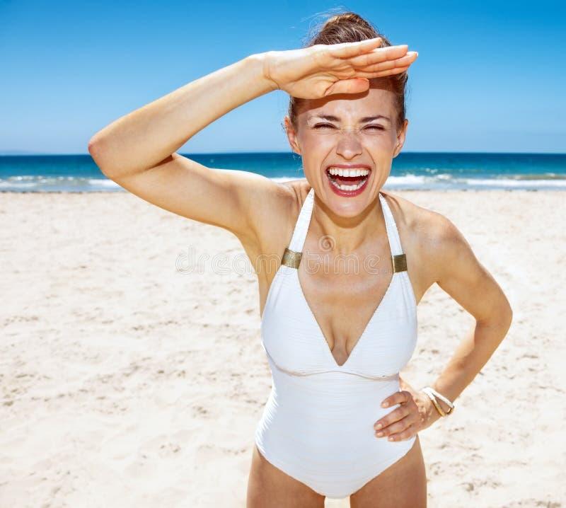 Nette Frau im weißen Badeanzug am sandigen Strand am sonnigen Tag stockfoto