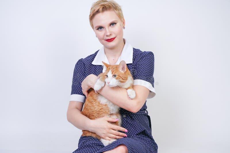 Nette nette Frau mit dem kurzen Haar im Pinuptupfenkleid, das ihr geliebtes Haustier auf einem weißen Hintergrund im Studio hält  stockfoto