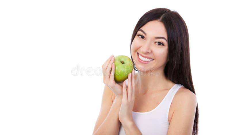 Nette Frau mit dem schönen schneeweißen Lächeln, das grünen Apfel hält Gesunder Lebensstil und Nahrung, nährend, Gewichtsverlust, stockfoto